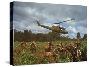 American UH1 Huey Helicopter Lifting Off as Personnel on the Ground Protect Themselves by Larry Burrows