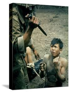 Bayonet Wielding South Vietnamese Soldier Menacing Captured Viet Cong Suspect During Interrogation by Larry Burrows