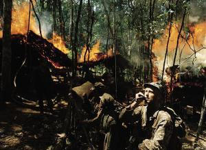 Captain Vernon Gillespie Contacting His Base Camp While Vietnamese Soldiers Burn Viet Cong Hideout by Larry Burrows