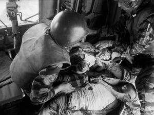Cpl. James Farley and Pfc. Wayne Hoilien Bandaging Sgt. Billie Owens' Shoulder, Yankee Papa 13 by Larry Burrows