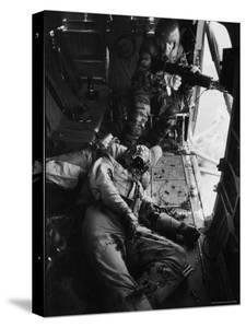 Helicopter Chief James C. Farley Working Jammed Machine as Pilot Lt. James Magel Dying Beside Him by Larry Burrows
