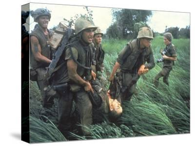 Marines Recovering Dead Comrade While under Fire During N. Vietnamese/Us Mil. Conflict