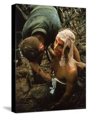 Shell Shocked American Marine Getting Wounds Bandaged in Muddy Jungle During OP Prairie