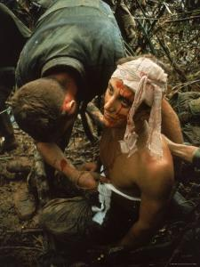 Shell Shocked American Marine Getting Wounds Bandaged in Muddy Jungle During OP Prairie by Larry Burrows