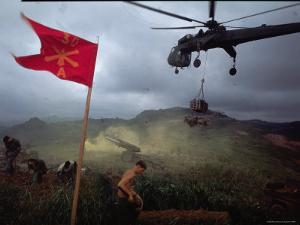 US 1st Air Cavalry Skycrane Helicopter Delivering Ammunition and Supplies to Besieged Marines by Larry Burrows