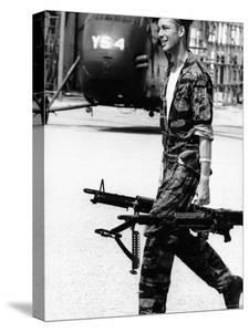 Yankee Papa 13 Helicopter Crew Chief James Farley Carrying a Pair of M-60 Machine Guns by Larry Burrows