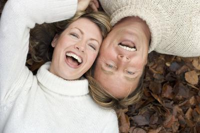 Laughing Couple Lying on Autumn Leaves-Ian Boddy-Photographic Print