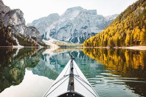 Beautiful View of Kayak on a Calm Lake with Amazing Reflections of Mountain Peaks and Trees by lbryan