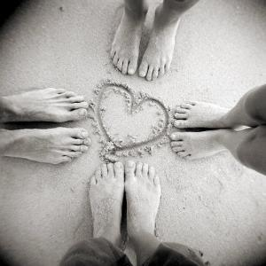 Four Pairs of Feet Standing around a Heart Shape Drawn in Sandy Beach, Taransay, Scotand, UK by Lee Frost