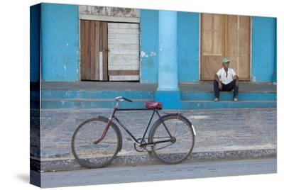 Old Bicycle Propped Up Outside Old Building with Local Man on Steps