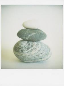 Polaroid of Three Sea-Worn Pebbles Piled Up Against a White Background by Lee Frost