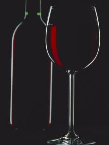 Studio Shot of Back-Lit Glass and Bottle of Red Wine by Lee Frost
