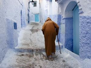 Old Man Walking in a Typical Street in Chefchaouen, Rif Mountains Region, Morocco by Levy Yadid
