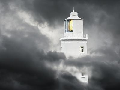 Lighthouse Emerging From Dark Clouds-Paul Hardy-Photographic Print