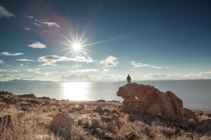 A Man Stands On A Rock On Antelope Island Overlooking The Great Salt Lake by Lindsay Daniels