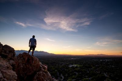 A Man Stands On A Rock Overlooking Salt Lake City, Utah by Lindsay Daniels