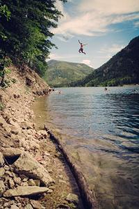 A Man Swings From A Rope Swing Into A Lake At Smith And Morehouse Reservoir, Utah by Lindsay Daniels