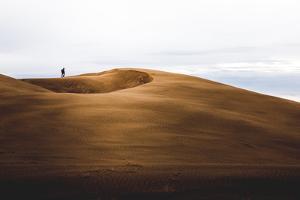 Man Walking On Sand Dunes In Little Sahara Recreation Area, Utah by Lindsay Daniels