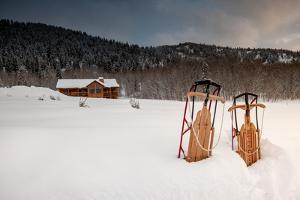 Two Classic Sleds In The Snow In Front Of A Cabin In The Mountains by Lindsay Daniels