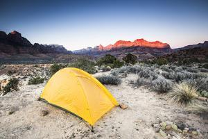 Yellow Tent And The Sun Setting On Background Cliffs And Mountains by Lindsay Daniels