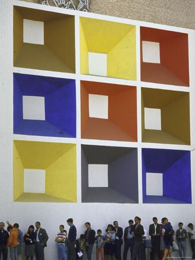 Line of People under Building Facade Painted with Brightly Colored Geometric Pattern-John Dominis-Photographic Print