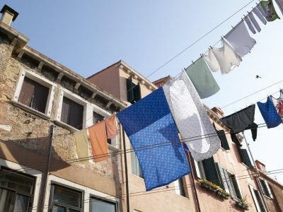 https://imgc.artprintimages.com/img/print/lines-of-laundry-from-brick-houses-blowing-in-the-breeze_u-l-q10x8cy0.jpg?p=0