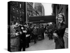 Actress Grace Kelly in Casual Pose with Armful of Roses Standing on Sidewalk During Shopping Trip by Lisa Larsen