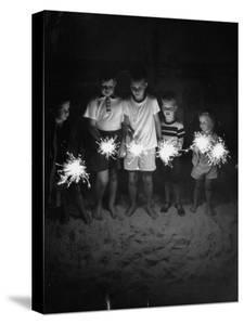 Children Holding Sparklers on a Beach by Lisa Larsen