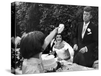 Flower Girl Janet Auchincloss Holding Up a Wedge of Wedding Cake for Bridegroom Sen. John Kennedy