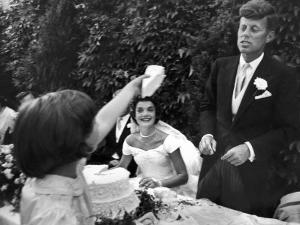 Flower Girl Janet Auchincloss Holding Up a Wedge of Wedding Cake for Bridegroom Sen. John Kennedy by Lisa Larsen