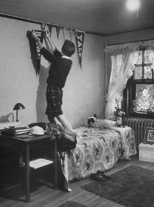 Freshman Mary Lloyd-Rees Hanging Both Harvard and Yale Banners in Her Room by Lisa Larsen