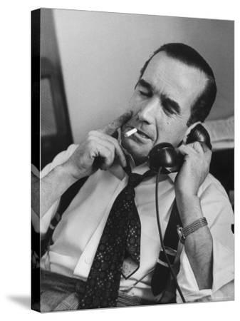 News Commentator, Edward R. Murrow with cigarette in mouth, tie loose, resting in his chair