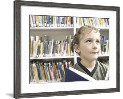 Little Boy Holding Blue Book in Library--Framed Photographic Print