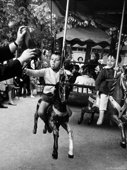 Little Boy on Merry Go Round at the Tuileries Gardens, Sticking Out His Tongue-Alfred Eisenstaedt-Photographic Print