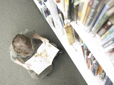 Little Boy Reading Book Beside Library Shelf--Photographic Print