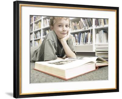 Little Boy Reading Book in Library--Framed Photographic Print