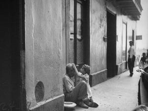 Little Girl Cleaning Face of a Street Beggar