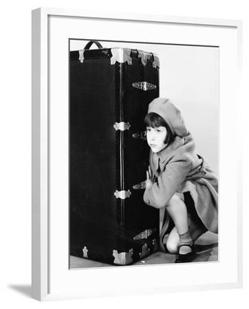 Little Girl in Hat and Coat Crouching Next to a Suitcase--Framed Photo