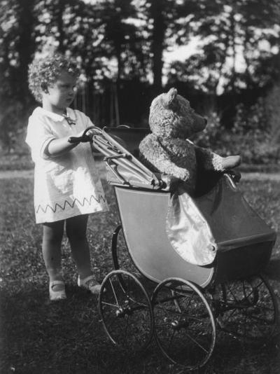 Little Girl Pushes Her Teddy Bear Around in a Pram--Photographic Print