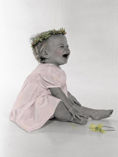 Little Girl Sitting and Laughing with a Floral Ring on Head and Two Flowers in Front of Her-Nora Hernandez-Giclee Print