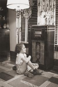Little Girl Smiles as She Enjoys a Radio Program in the 1930s