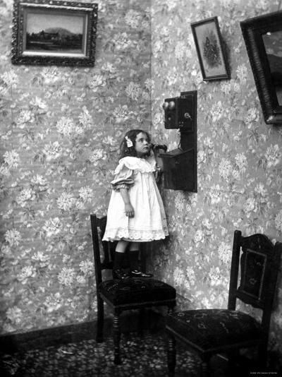 Little Girl Standing on Chair to Speak to Her Mother in Heaven by Telephone--Photographic Print