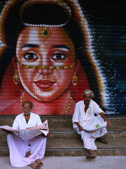 Local Men Read Newspapers in Front of Painted Shutter, Kozhikode, Kerala, India-Greg Elms-Photographic Print