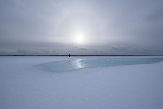 Lonely Person in Icelandic Lowlands with Blue Puddle of Water and Sun in the Background, Winter-Niki Haselwanter-Photographic Print