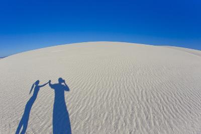 Long Shadows of a Couple Holding Hands Cast on a Rippled Sand Dune-Mike Theiss-Photographic Print