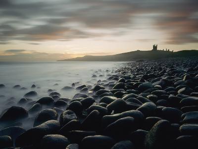 Looking Along Boulder Covered Beach Towards Dunstanburgh Castle at Dawn-Design Pics Inc-Photographic Print