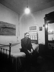 """Author William Burroughs, an Ex Dope Addict, Relaxing on a Shabby Bed in a """"Beat Hotel"""" by Loomis Dean"""