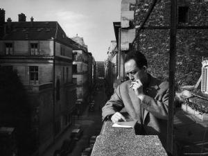 French Writer Albert Camus Smoking Cigarette on Balcony Outside His Publishing Firm Office by Loomis Dean