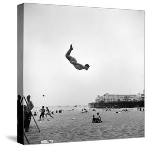Man Flying Off a Trampoline at Santa Monica Beach by Loomis Dean