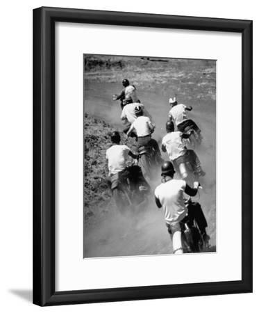 Riders Enjoying Motorcycle Racing, Leaving a Trail of Dust Behind